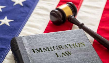 Immigration law text on black book and judge gavel on US of America flag background. Migration, emigration visa in USA concept 免版税图像 - 150367918