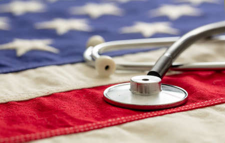 USA health care. Medical stethoscope on a US of America flag, closeup view. American health insurance  concept 免版税图像 - 150367920