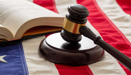 Law studies in USA. Judge gavel and open book on US of America flag background. Justice in USA concept