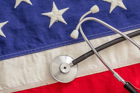 USA health care. Medical stethoscope on a US of America flag, top view. American health insurance  concept 免版税图像