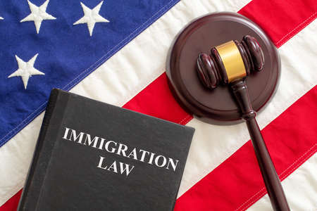 Immigration law text on black book and judge gavel on US of America flag background, top view. Migration, emigration visa in USA concept