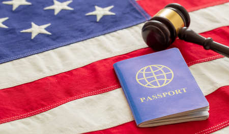 Blue passport and judge gavel on USA flag background, closeup view. Immigration, United States of America visa concept