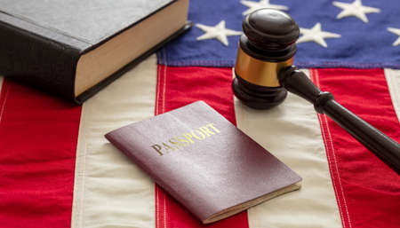 Passport and judge gavel on USA flag background, closeup view. Immigration, United States of America visa concept 免版税图像