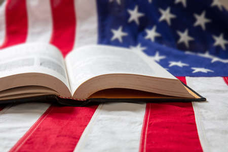 Book open on USA flag background, closeup view. United States of America education, culture, religion concept