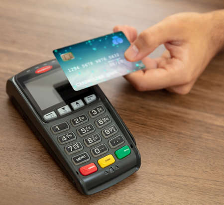 Payment with NFC technology. Hand holding a credit card over a POS terminal, wooden counter background, closeup view.Terminal cash register machine for contactless payment.