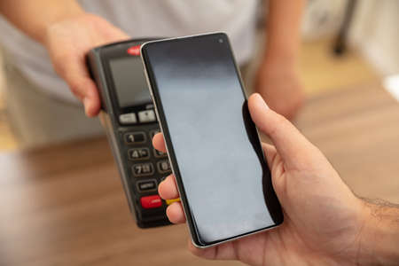 Mobile payment, smart phone nfc, near field communication wireless technology. Cashier and customer hands with POS machine and smartphone, closeup view