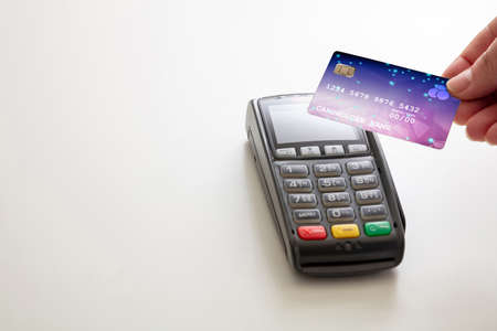 Payment with NFC technology. Hand holding a credit card over a POS terminal isolated on white background, closeup view.Terminal cash register machine for contactless payment. 免版税图像