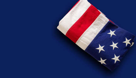 USA flag folded on blue background. American flag top view, copy space. Memorial day and 4th of July, Independence day concept. Card, poster template