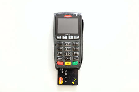 Athens, Greece. June 27, 2020. Wireless POS payment terminal Ingenico with credit card Mastercard isolated on white background, top view.