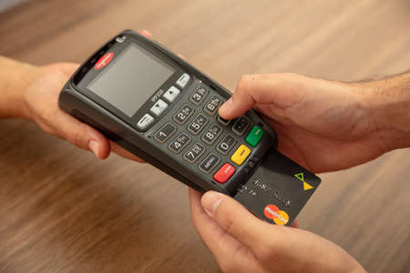 Athens, Greece. June 27, 2020. Wireless POS payment terminal Ingenico with credit card Mastercard isolated on white background, close up view.