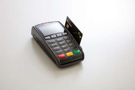 Athens, Greece. June 27, 2020. Wireless POS payment terminal Ingenico with credit card Payoneer isolated on white background, close up view.