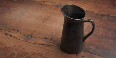 Jug against wood table background. Milk pitcher, metal container with handle to hold liquids, above view, copy space. 3d illustration Banco de Imagens