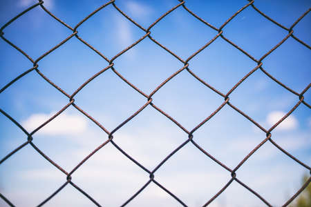 Blue sky with clouds through rusty wire mesh fence. Protection border and forbidden line. Blur background, texture. Close up view of link cage, wallpaper.