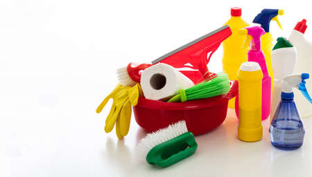 Cleaning products against white background. Plastic chemical detergent bottles and equipment, copy space. Domestic household or business sanitary cleaning
