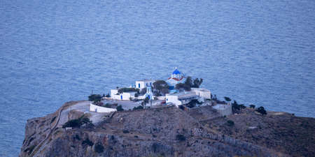Greek island monastery, white and blue colors, traditional architecture. Church and auxiliary buildings on the top of a rocky hill, sea background. Greece. Kea island, Kastriani monastery.