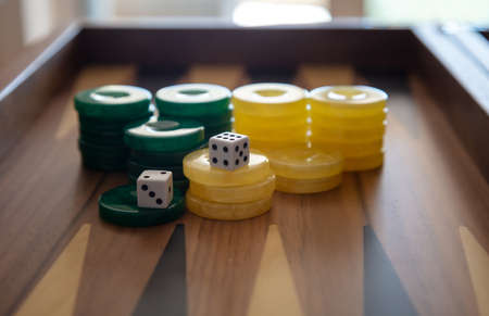 Backgammon, playing an ancient table game. Dice and chips on the backgammon board. Strategy and luck, leisure, entertainment concept.