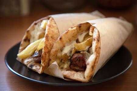 Gyro pita, shawarma, take away, street food. Two pita bread wraps with meat, traditional greek turkish food on wooden table, closeup Standard-Bild