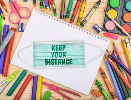 KEEP YOUR DISTANCE text message on a medical protective mask, school supplies flat lay, Back to school, coronavirus days