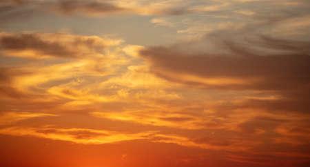 Sunset orange cloudscape background. Dramatic magical sunrise over orange cloudy sky. Twilight, dawn