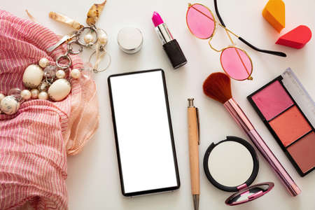 Woman accessories and smartphone with blank white screen against white color background, flat lay, top view. Fashion blogger workspace, copy space 免版税图像