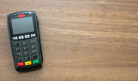 POS terminal isolated on wooden background, top view.Terminal cash register machine for contactless payment with credit card. Banking equipment, NFC.