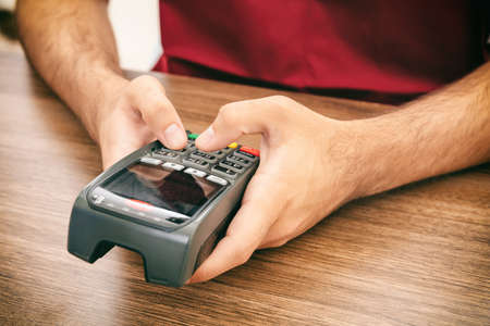 Man holding a payment swipe machine and typing, closeup view. Credit card reader, POS terminal payment concept.