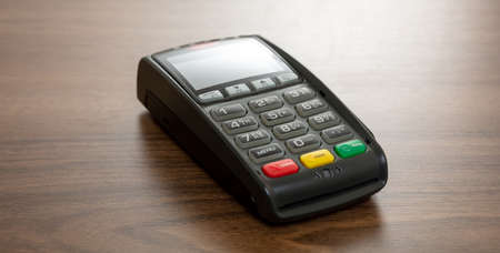 POS terminal isolated on wooden background, copy space.Terminal cash register machine for contactless payment with credit card. Banking equipment, NFC.