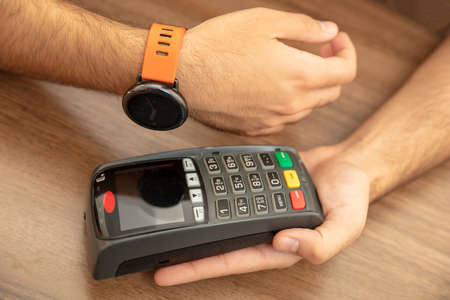 Mobile payment, smart watch nfc, near field communication wireless technology. Cashier and customer hands with POS machine and smart watch, closeup view