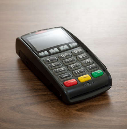 POS terminal isolated on wooden background, closeup view.Terminal cash register machine for contactless payment with credit card. Banking equipment, NFC. 免版税图像