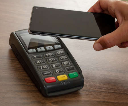 Mobile payment, smart phone nfc, near field communication wireless technology. Customer hand holding a smartphone close to a POS terminal, closeup view