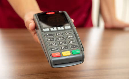 Cashier offers POS terminal for payment with credit card. Banking, shopping and contactless payment with NFC technology concept.
