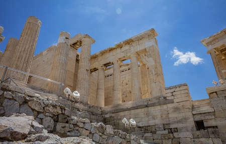 Athens Acropolis, Greece landmark. Propylaea entrance gate empty, Ancient Greek columns and stairs, low angle view, blue cloudy sky. 免版税图像