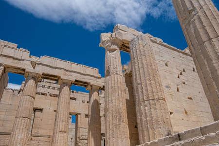 Athens Acropolis, Greece landmark. Ancient Greek pillars low angle view at Propylaea entrance gate, blue cloudy sky.