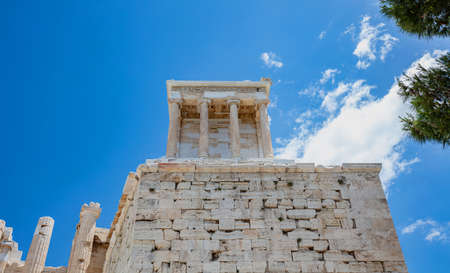 Athens Acropolis, Greece landmark. The Temple of Athena Nike low angle view at Propylaea gate entrance, blue cloudy sky in a spring sunny day. 免版税图像