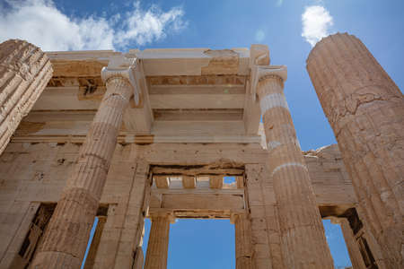 Athens Acropolis, Greece landmark. Ancient Greek Propylaea entrance gate ceiling and pillars low angle view, blue sky, spring sunny day.