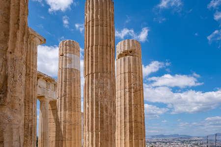 Athens Acropolis, Greece landmark. Ancient Greek columns pillars at Propylaea entrance gate closeup, city view and blue cloudy sky.