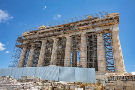 Athens Acropolis, Greece. Parthenon temple front view, scaffolded facade for restoration works, blue sky, low angle view