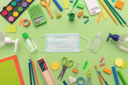 School supplies, medical protective mask blank and sanitizer gel on pastel green color background, top view, Back to school, coronavirus days. Template, copy space