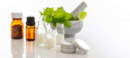 Alternative herbal medicine. Homeopathic globules, fresh mint herb isolated against white background. Aromatherapy, Homeopathy natural products
