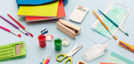 School supplies, medical protective mask and sanitizer gel on pastel blue color background, closeup view, Back to school, coronavirus days.
