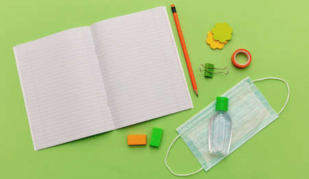 Open blank school notebook, medical protective mask and hand sanitizer gel on pastel green background, top view, Back to school, coronavirus days. Template, copy space 免版税图像