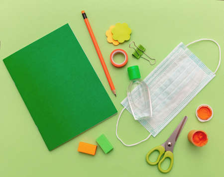 Back to school, coronavirus days. Medical protective mask, hand sanitizer gel and blank notebook on green color background, top view, Template, copy space 免版税图像