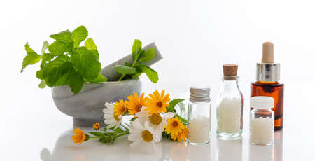 Alternative herbal medicine. Homeopathic globules, fresh wild flowers and herbs isolated against white background. Aromatherapy, Homeopathy natural products