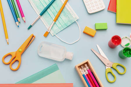 School supplies, medical protective mask and sanitizer gel on pastel blue color background, top view, Back to school, coronavirus days flat lay.
