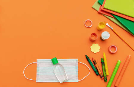 School supplies, medical protective mask and sanitizer gel on orange color background, top view, Back to school, coronavirus days. Template, copy space