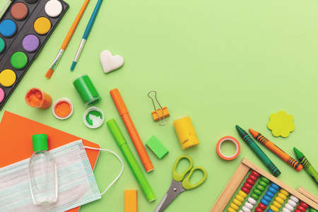 School supplies, medical protective mask and sanitizer gel on pastel green color background, top view, Back to school, coronavirus days flat lay.
