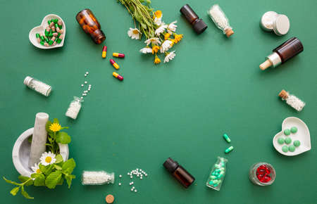 Alternative herbal medicine. Homeopathic globules, fresh wild flowers and herbs flat lay on green background. Aromatherapy, Homeopathy natural products