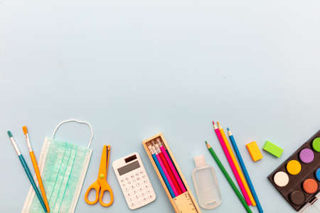 School supplies, medical protective mask and sanitizer gel on pastel blue color background, top view, Back to school, coronavirus days. Template, copy space