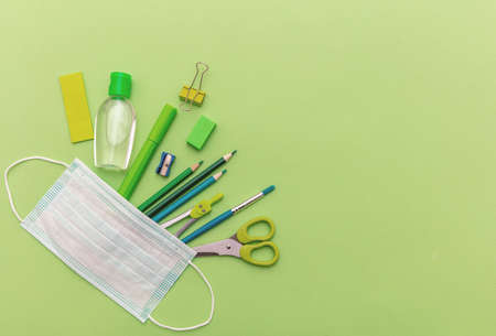 Back to school, coronavirus days. Medical protective mask, hand sanitizer gel and school supplies on pastel green color background, top view, Template, copy space 免版税图像