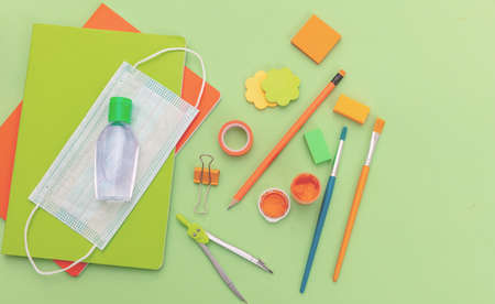 Coronavirus spread prevention measure at school. Medical mask, alcohol hand disinfection gel and school supplies on pastel green color background, top view